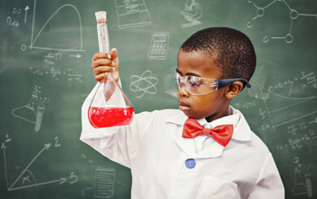 a boy in a lab coat with a red bowtie in front of a blackboard holding a flask with a red liquid inside.