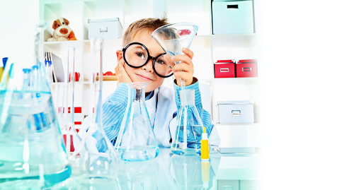 A boy with glasses in a lab with beakers holding a funnel inside of a beaker