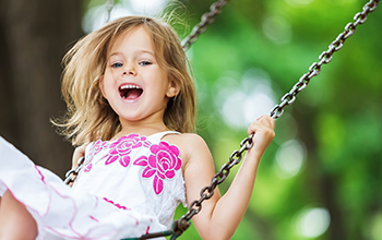 Girl in flowered dress having fun on a swing